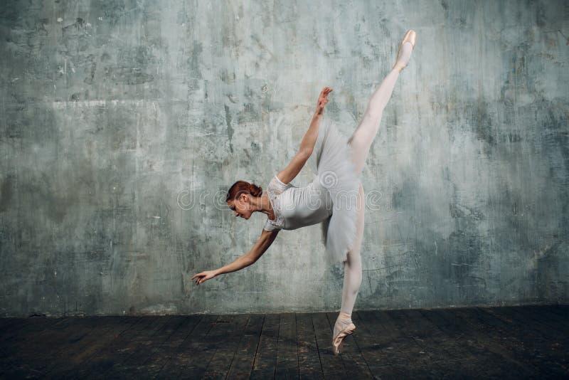 Ballerinakvinnlig Ung härlig kvinnabalettdansör, iklädd yrkesmässig dräkt, pointeskor och vit ballerinakjol royaltyfri foto