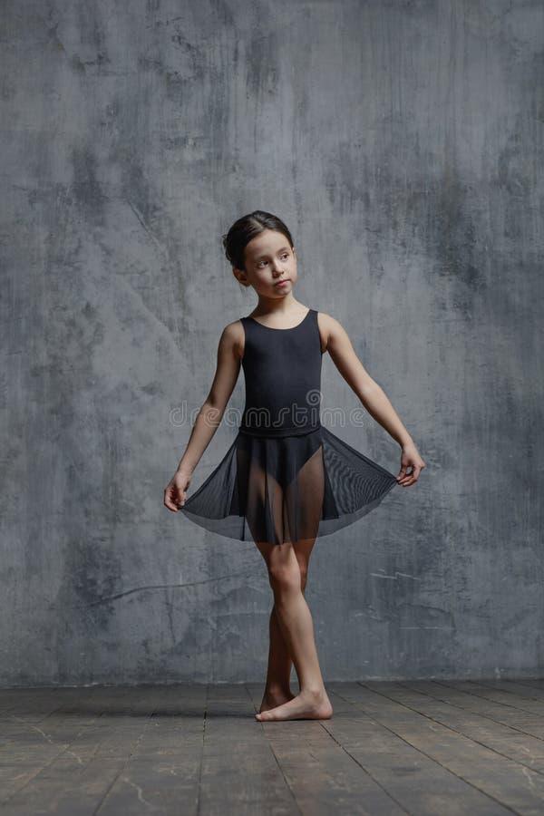 Ballerinameisje het stellen in dansstudio stock afbeeldingen