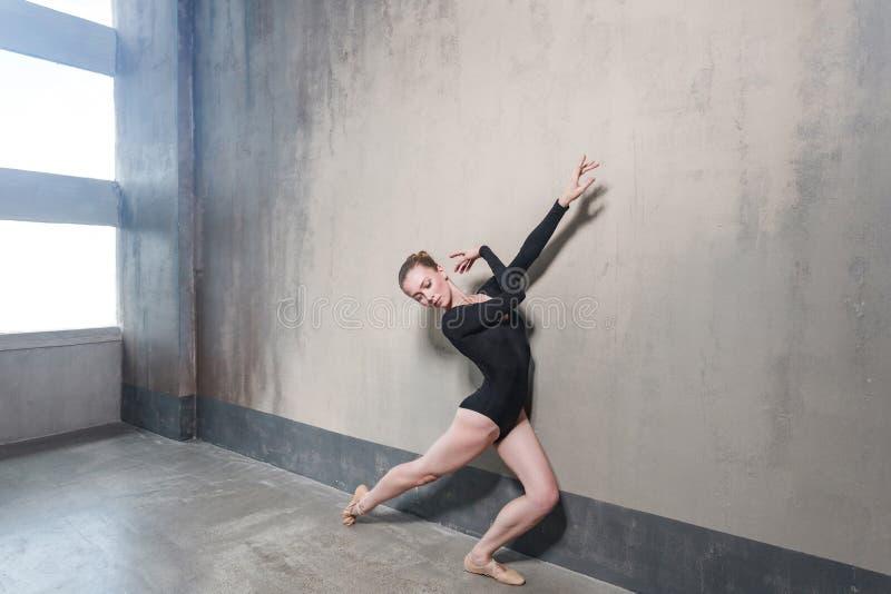 Ballerinarörelse i klassisk balett som poserar nära fönster arkivfoton