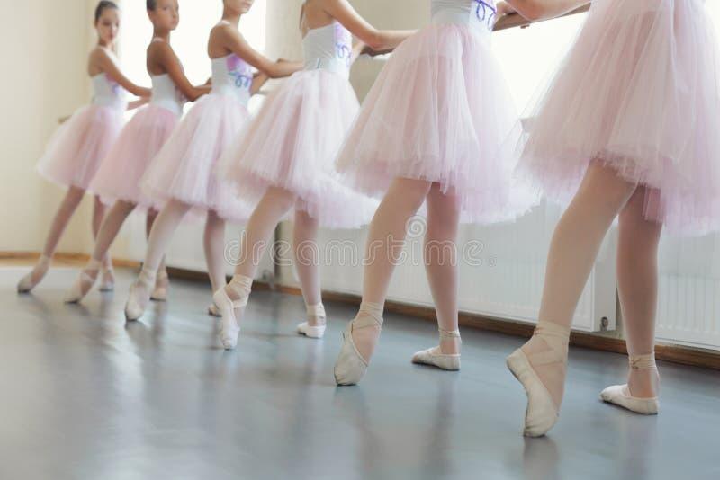 Ballerinas having practice near ballet barre at hall royalty free stock image