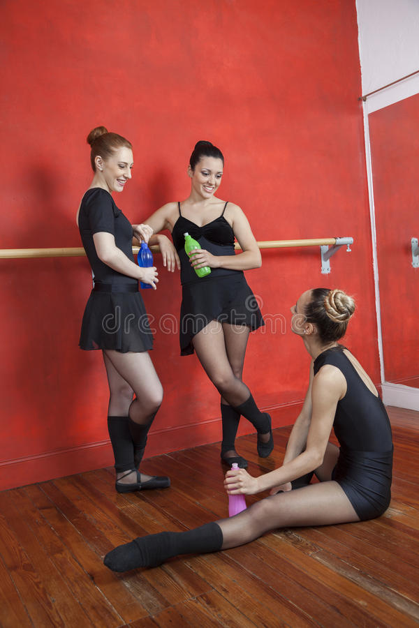 Free Ballerinas Looking At Friend While Holding Bottles In Studio Royalty Free Stock Image - 73327426