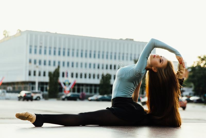 Ballerinasammanträde i gymnastiskt poserar i mitt av stadsgatan Byggnadsbakgrund arkivbilder