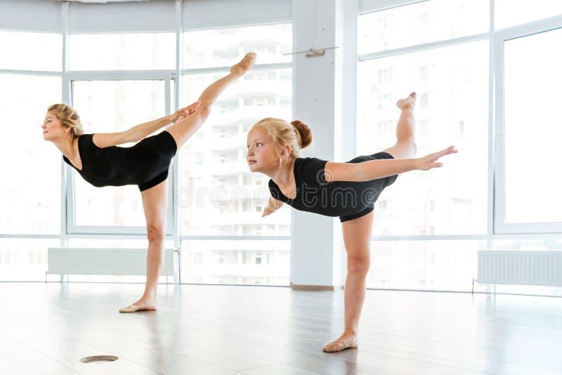 Ballerinatanzen der Frau und des kleinen Mädchens in der Ballettschule stockbild