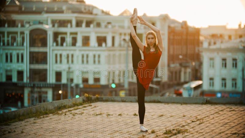 Ballerinautbildning för ung kvinna på taket - anseendet i poserar uppvisning henne som sträcker royaltyfri bild