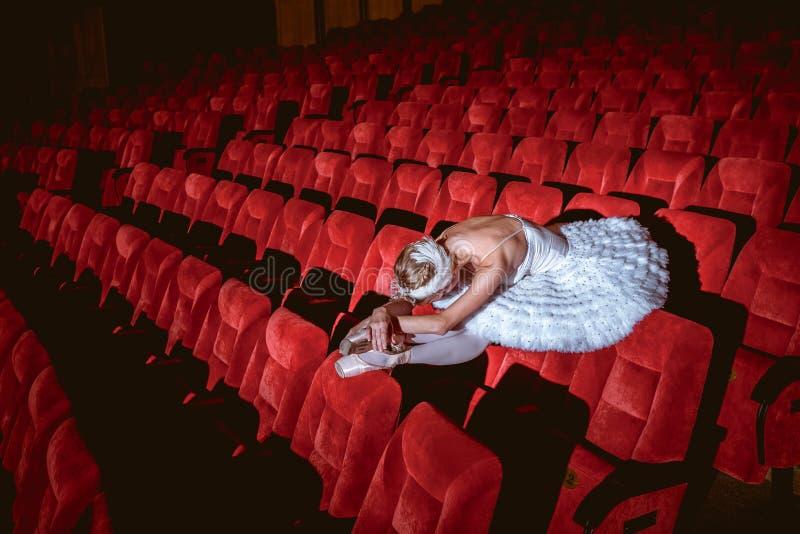 Ballerinazitting in het lege auditoriumtheater royalty-vrije stock afbeelding