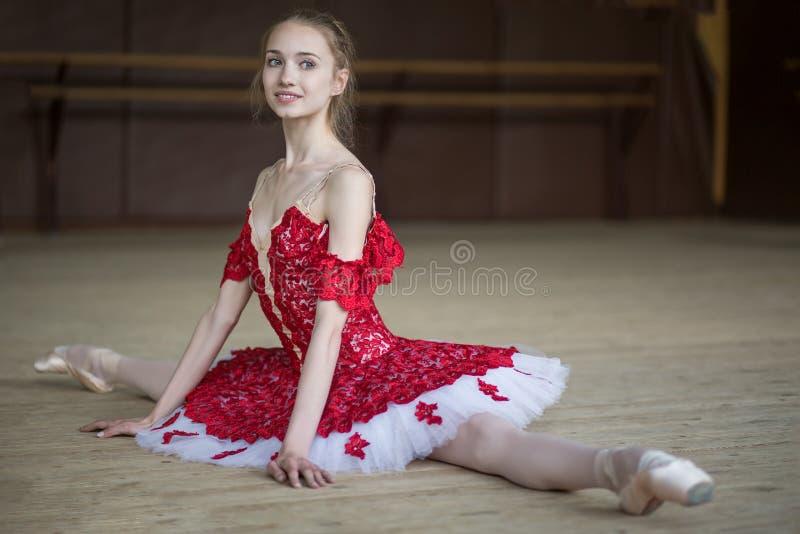 Ballerinazitting op de vloer in de spleten die zich in rode tut kleden royalty-vrije stock afbeeldingen