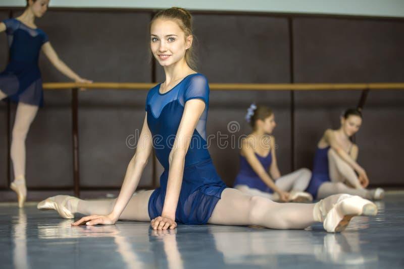 Ballerinazitting op de vloer in de spleten in een dansklasse DA stock foto