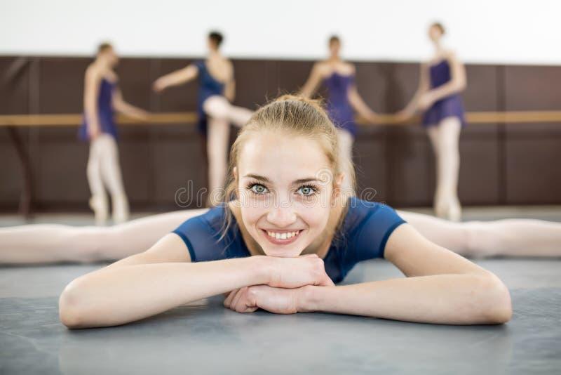 Ballerinazitting op de vloer met zijn gezicht aan de camera in Th stock foto