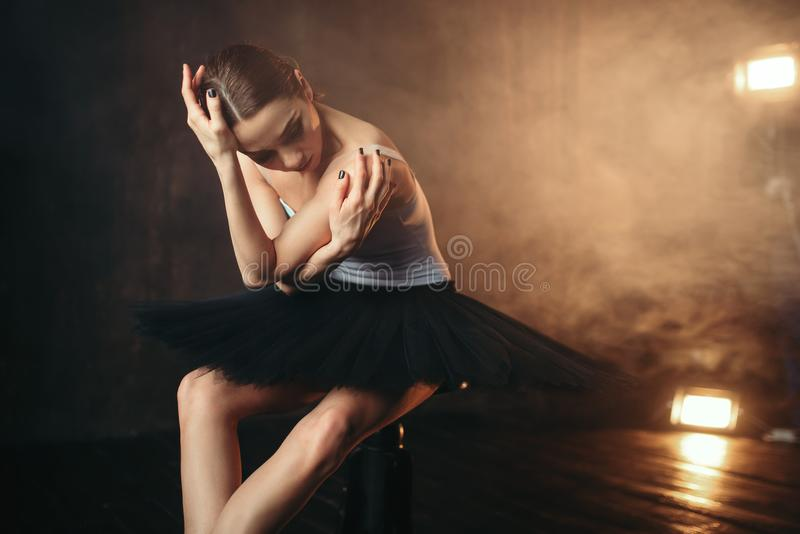Ballerinazitting op zwarte banquette in theater stock foto