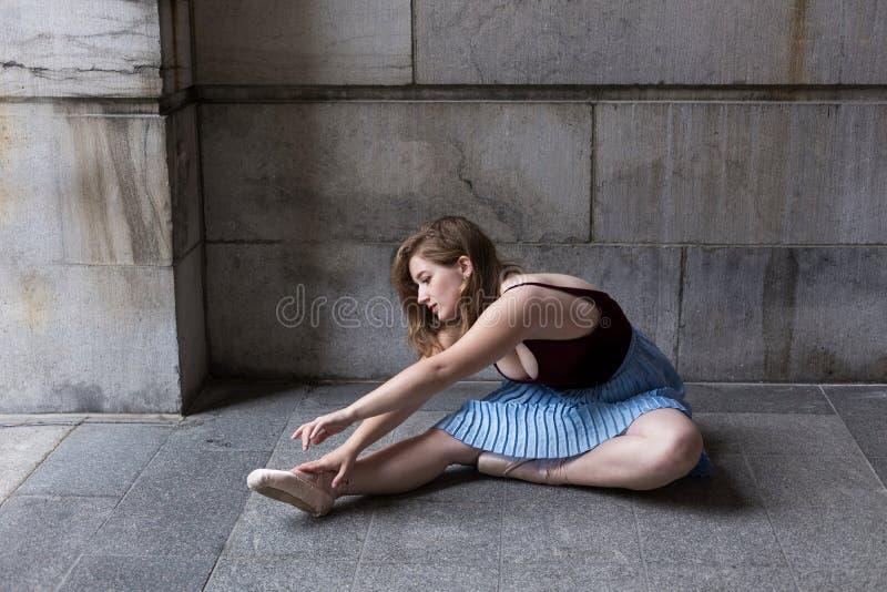 Ballerinazitting in profiel bij zich steenportiek het uitrekken over haar pointeschoenen royalty-vrije stock foto