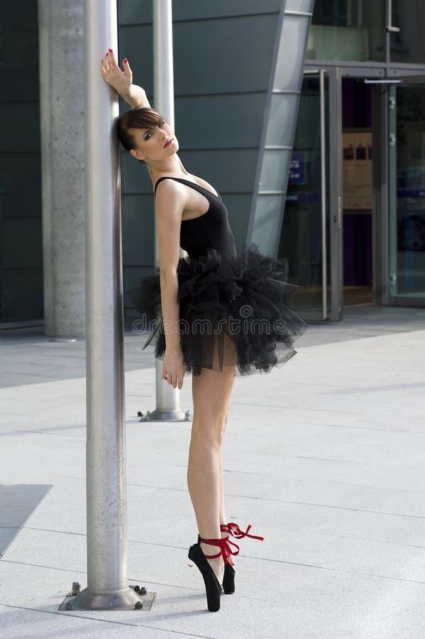 Ballerine dans le tutu noir près d'un pôle image stock