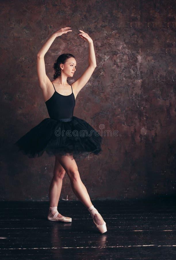 Ballerine de danseur classique dans la belle jupe noire de tutu de robe posant dans le studio de grenier photo stock