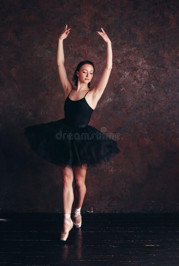 Ballerine de danseur classique dans la belle jupe noire de tutu de robe posant dans le studio de grenier images libres de droits