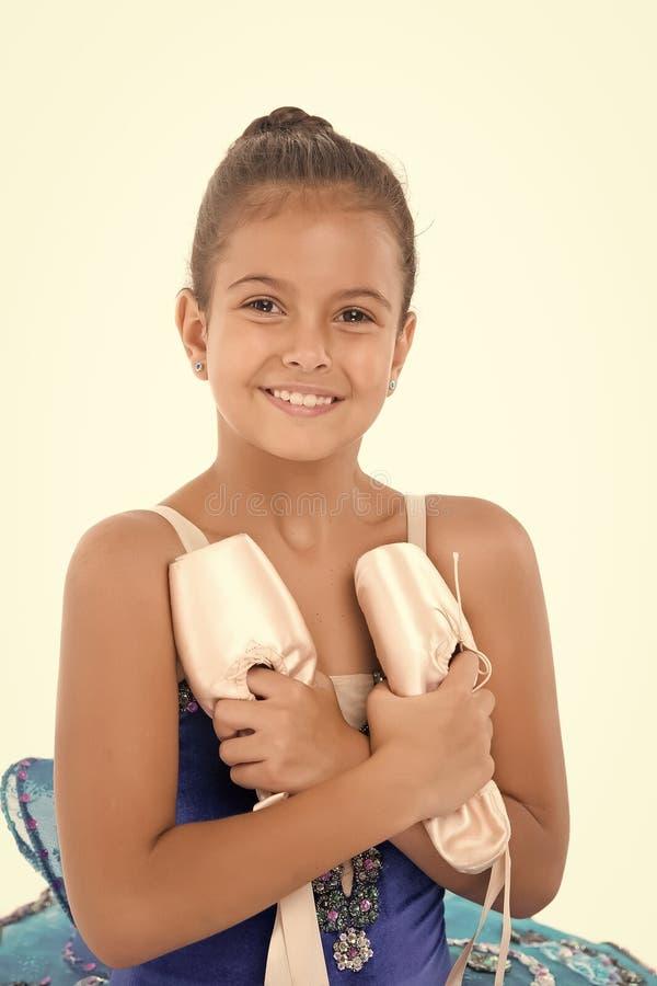 Ballerine heureuse d'attribut important de chaussures de ballet de prises d'enfant excellente La ballerine de fille tient le blan photographie stock libre de droits