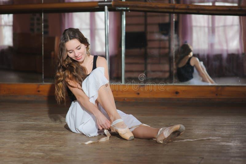 Ballerine mettant sur ses chaussures de ballet photo stock