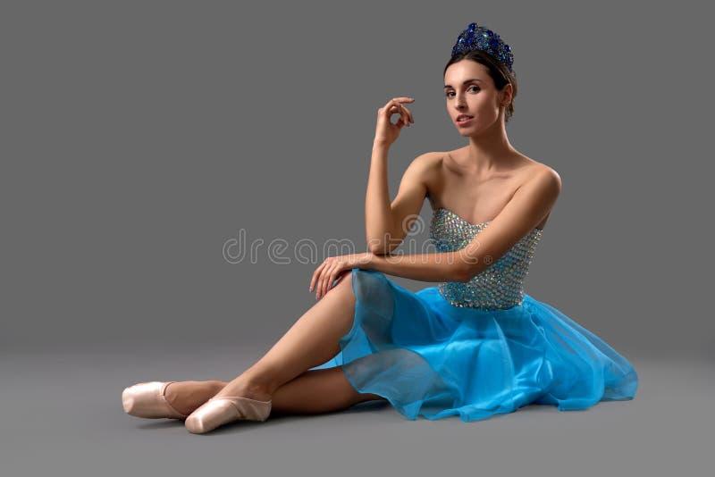 Ballerine mince dans la robe bleue se reposant sur le plancher dans le studio photo stock
