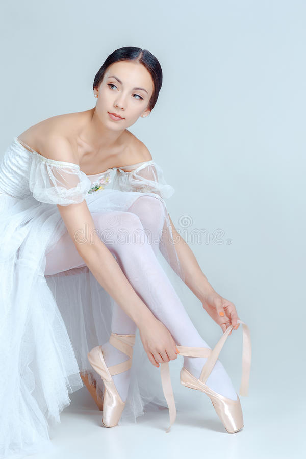 Ballerine professionnelle mettant sur ses chaussures de ballet images stock