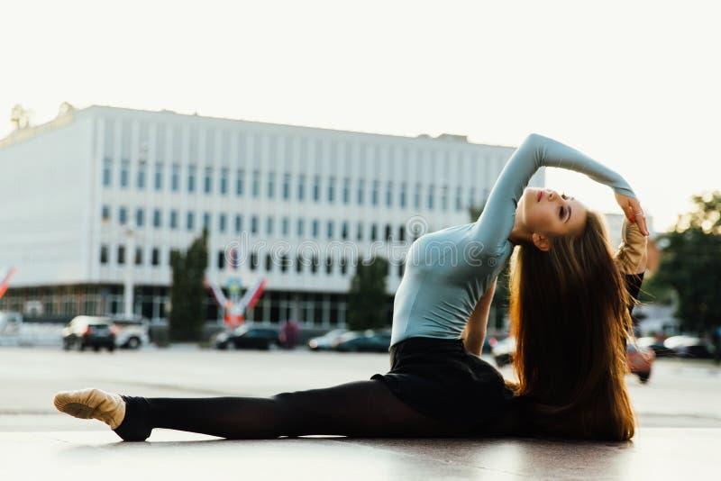 Ballerine s'asseyant dans la pose gymnastique au milieu de la rue de ville Fond de bâtiments images stock
