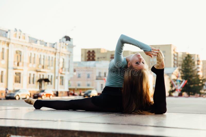 Ballerine s'asseyant dans la pose gymnastique au milieu de la rue de ville Fond de bâtiments photo stock