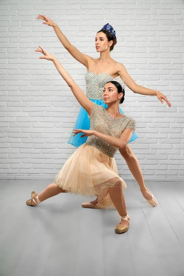 Ballerinen in den beige und blauen Kleidern, die oben im Studio schauen lizenzfreie stockfotos