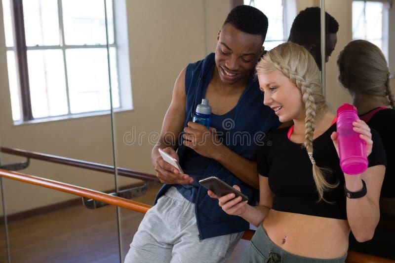 Ballerini sorridenti che utilizzano telefono nello studio fotografia stock libera da diritti