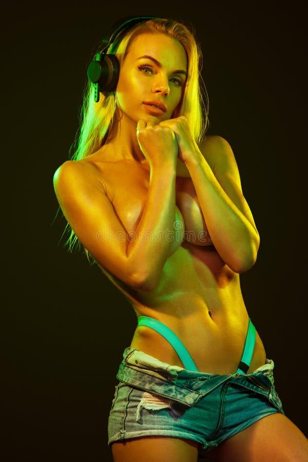 Ballerino adatto topless ed atleta della donna con le catene che posano sul fondo nero con le luci variopinte fotografia stock libera da diritti