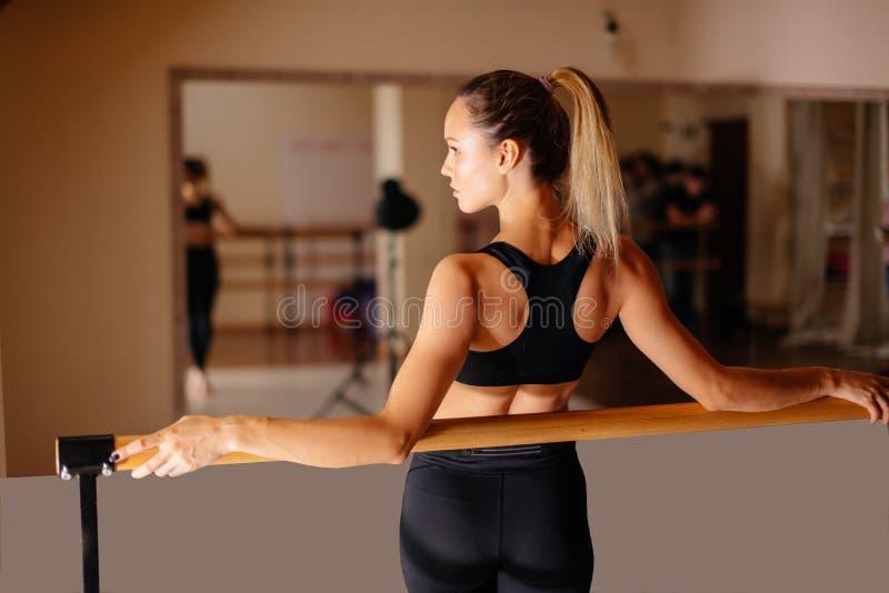 Ballerino della donna che posa vicino alla sbarra nello studio di balletto immagini stock libere da diritti