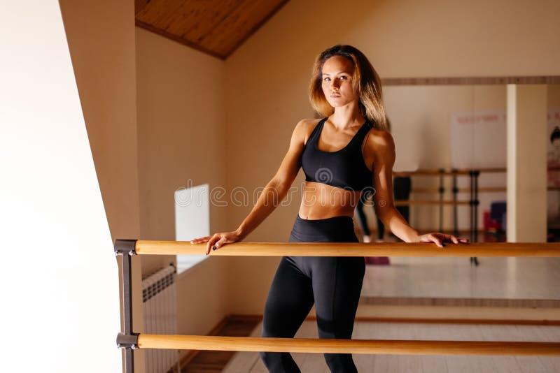 Ballerino della donna che posa vicino alla sbarra nello studio di balletto fotografia stock