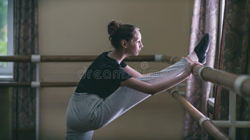 Ballerino della ragazza che fa gli esercizi nella classe di ballo al banco fotografia stock libera da diritti