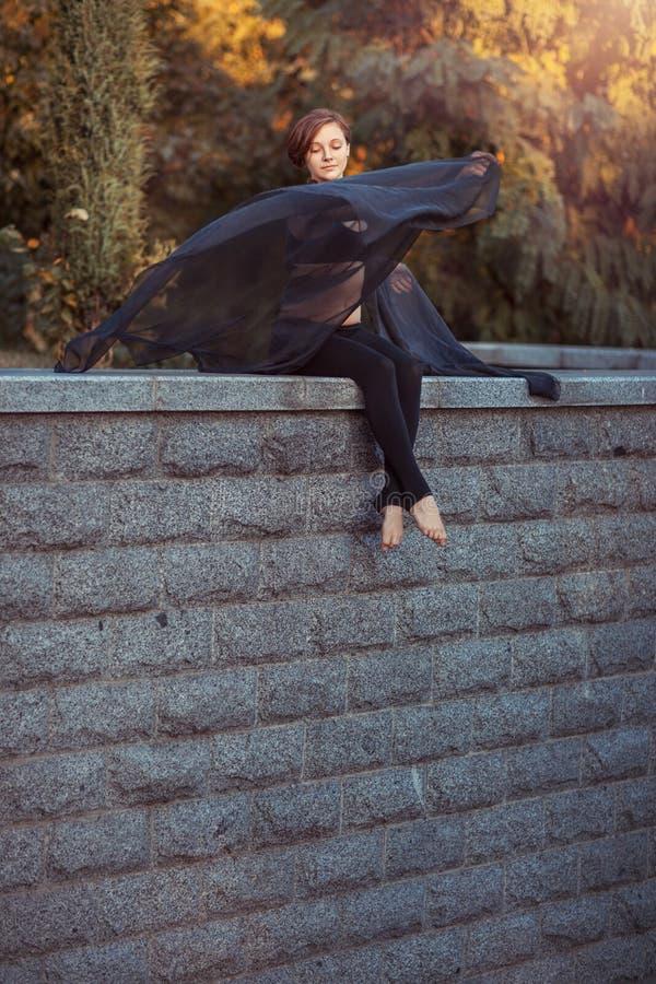 Ballerino della ragazza con lo scialle nero che si siede su una parete di pietra fotografia stock