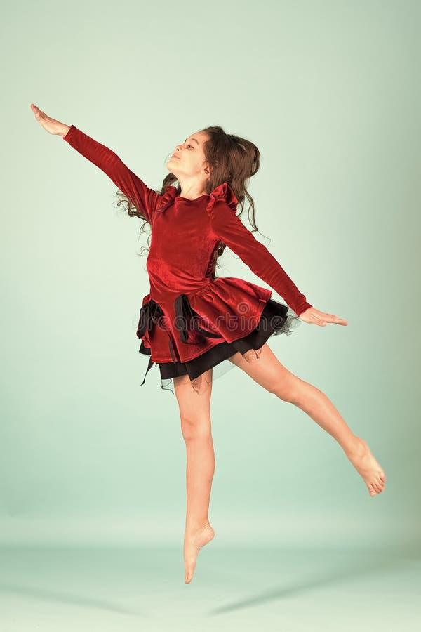 Ballerino della ragazza nel ballo rosso del vestito a piedi nudi su fondo blu fotografia stock libera da diritti