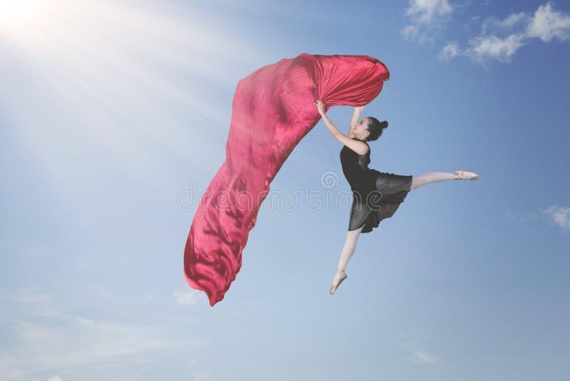 Ballerino di balletto che balla con il tessuto nel cielo fotografia stock