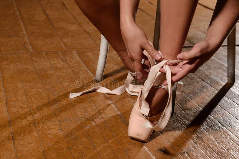 Ballerino di balletto che lega le pantofole intorno al suo pointe della ballerina della donna della caviglia fotografie stock