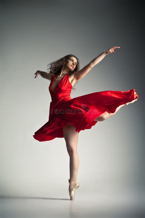 Ballerino di balletto che porta vestito rosso sopra grey immagine stock libera da diritti