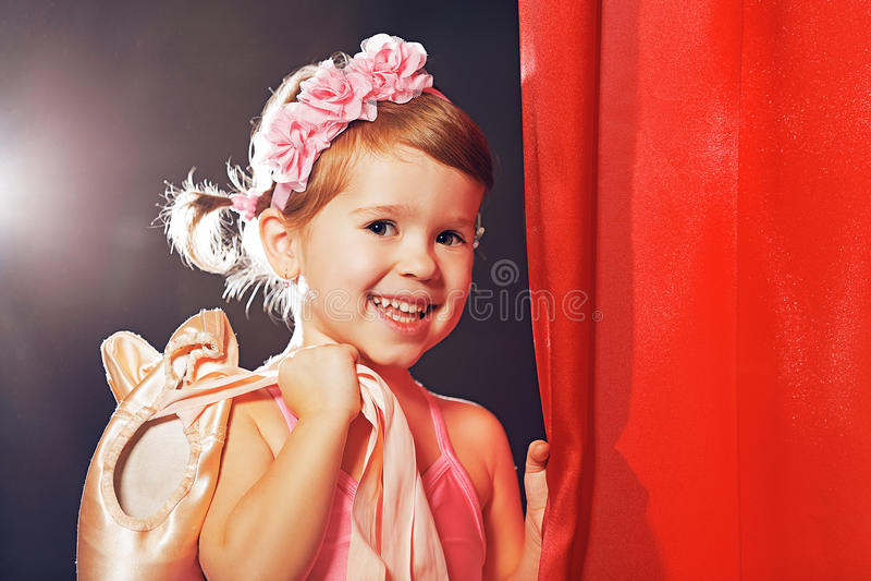 Ballerino di balletto della ballerina della bambina in scena nelle scene laterali rosse immagini stock