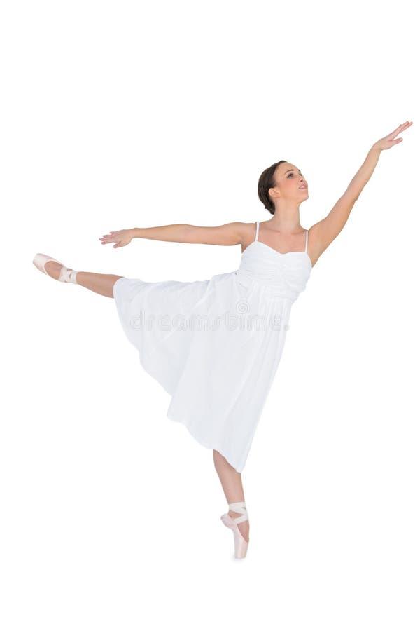 Ballerino di balletto messo a fuoco che posa sulla sua punta dei piedi mentre aumentando una gamba fotografia stock libera da diritti