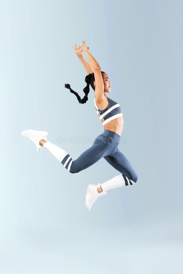 Ballerino emozionante attraente della ragazza di forma fisica nel salto di sportwear della gioia isolato sopra fondo grigio fotografia stock