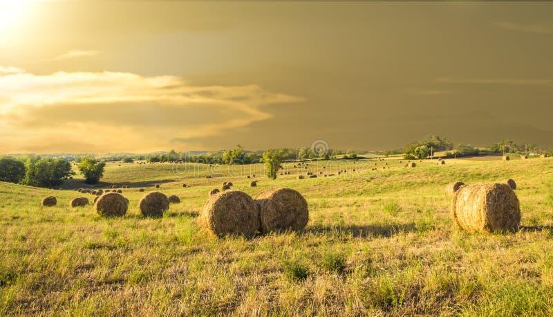 Balles de foin à une ferme au coucher du soleil photo stock