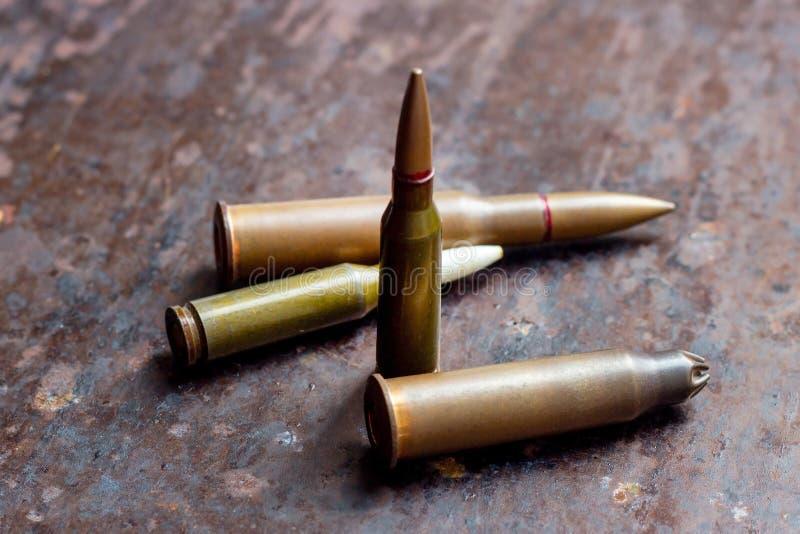 Balles diverses d'arme sur le fond rouillé en métal Industrie militaire, guerre, commerce d'armes global et concept de crime photos stock