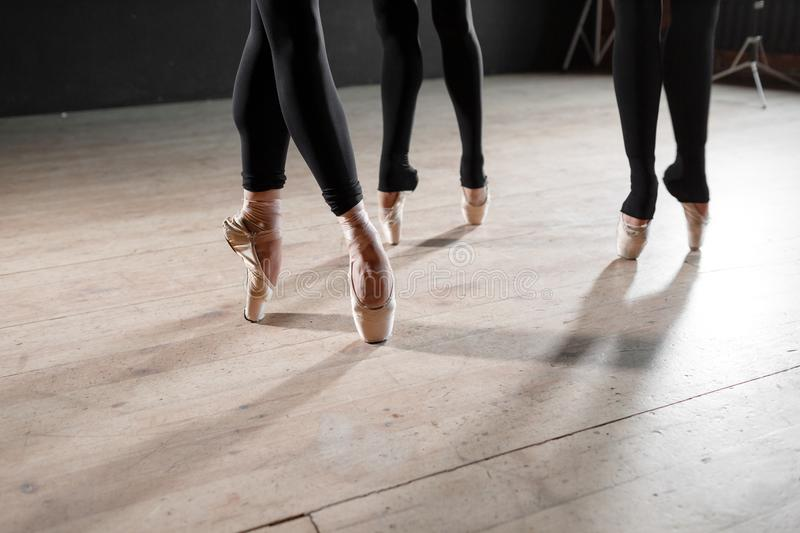 The ballet concept. Pointe shoes close up. Young ballerina girls. Women at the rehearsal in black bodysuits. Prepare a. Young ballerina girls. Women at the royalty free stock images
