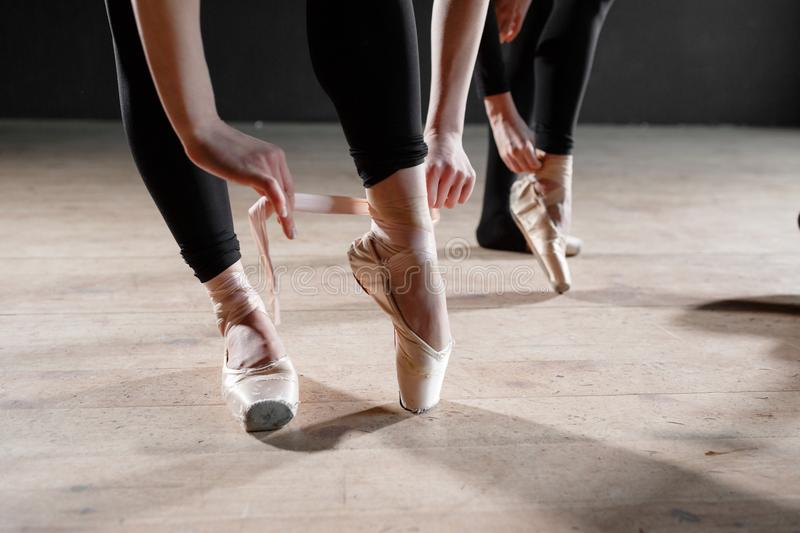 The ballet concept. Pointe shoes close up. Young ballerina girls. Women at the rehearsal in black bodysuits. Prepare a. Young ballerina girls. Women at the royalty free stock photography