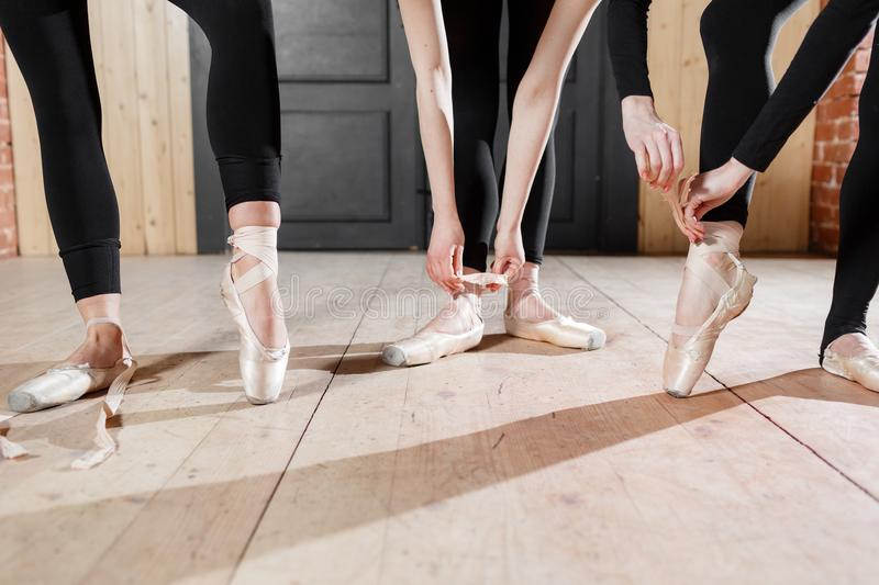 The ballet concept. Pointe shoes close up. Young ballerina girls. Women at the rehearsal in black bodysuits. Prepare a. Young ballerina girls. Women at the royalty free stock photo