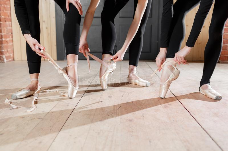 The ballet concept. Pointe shoes close up. Young ballerina girls. Women at the rehearsal in black bodysuits. Prepare a. Young ballerina girls. Women at the royalty free stock image