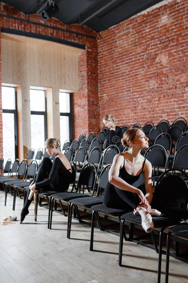 The ballet concept. Young ballerina girls sitting on the black chairs in the hall. Women at the rehearsal in black. Young ballerina girls. Women at the rehearsal royalty free stock photo