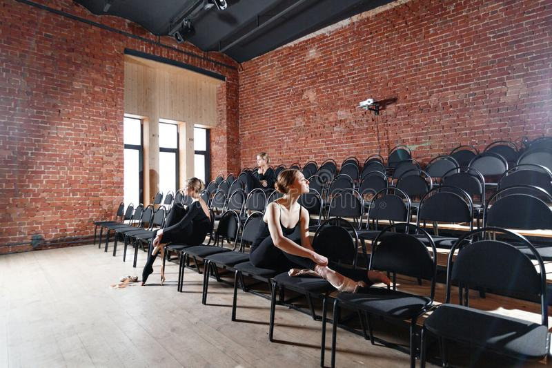 The ballet concept. Young ballerina girls sitting on the black chairs in the hall. Women at the rehearsal in black. Young ballerina girls. Women at the rehearsal royalty free stock photos
