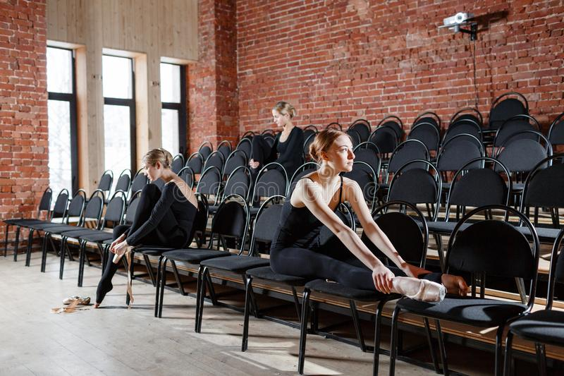 The ballet concept. Young ballerina girls sitting on the black chairs in the hall. Women at the rehearsal in black. Young ballerina girls. Women at the rehearsal stock photography