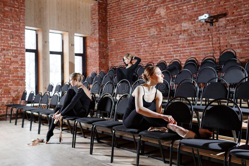 The ballet concept. Young ballerina girls sitting on the black chairs in the hall. Women at the rehearsal in black. Young ballerina girls. Women at the rehearsal royalty free stock image