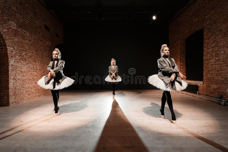 The ballet concept. Young ballerina girls. Women at the rehearsal in a white tutu and a grey jacket. Prepare a. Theatrical performance Brick walls and interior royalty free stock image