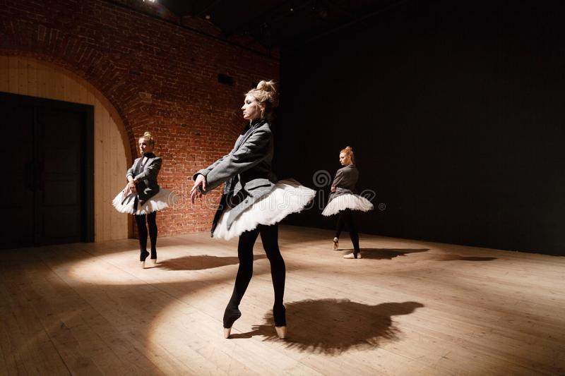 The ballet concept. Young ballerina girls. Women at the rehearsal in a white tutu and a grey jacket. Prepare a. Theatrical performance Brick walls and interior royalty free stock images