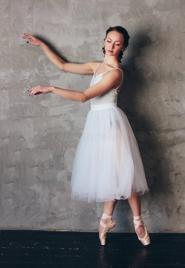 Ballet dancer ballerina in beautiful light blue dress tutu skirt posing in loft studio royalty free stock photography